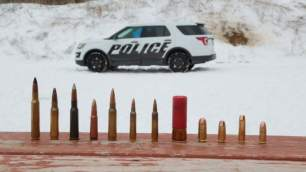 In this photo provided by Ford Motor Company, different types of ammunition used in testing are displayed, foreground, as a Ford Police Interceptor Utility vehicle sits parked in the background during ballistic testing of doors against small arm fire at the Livingston Conservation and Sports Association in Brighton, Mich.