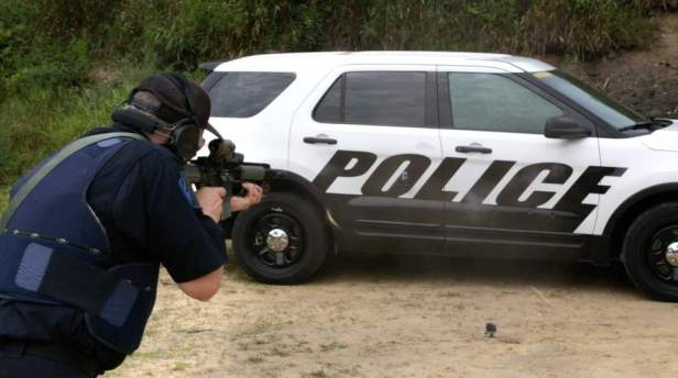 In this photo provided by Ford Motor Company, a Michigan State Police officer shoots at the doors of a Ford Police Interceptor Utility vehicle during ballistic testing of doors against small arm fire at the Barry County Conservation Club in Hastings, Mich.